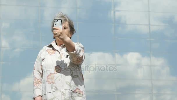 Zralá žena má fotografie pomocí chytrého telefonu