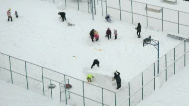 People play on fenced courtyard in winter