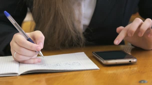 Iskoláslány egy arany intelligens telefon használata. Közeli kép: