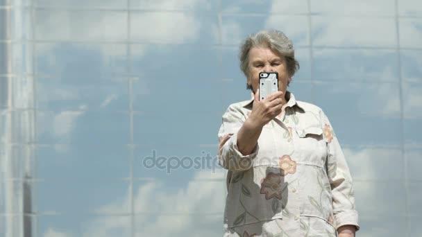 Starší žena bere fotografií pomocí stříbrné smartphone