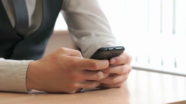 Neznámý mladý muž, který držel černý smartphone