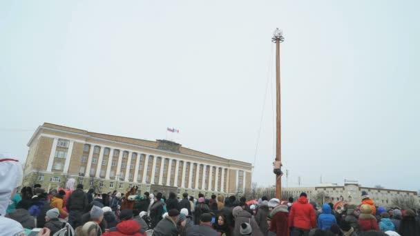 Muž vyšplhání pilíř během masopustu karneval