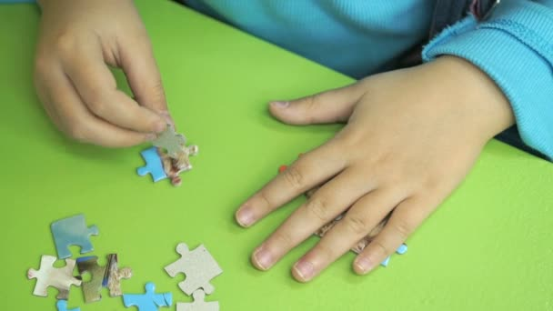 Unknown child collecting puzzles at the table