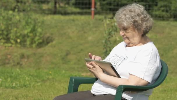 alte Frau hält ein silbernes Computertablett im Freien