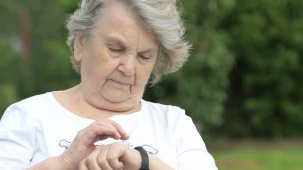 Seniorin blickt auf Fitness-Tracker am Armband