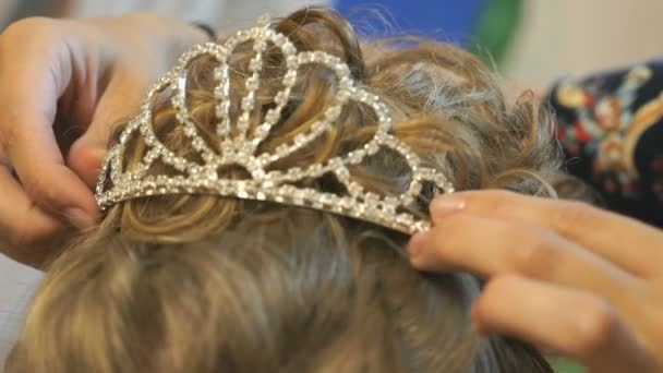 Stylist dresses crown on head of model. Close-up