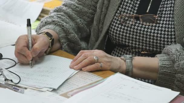 Neidentifikovaný učitel chechs úkol v poznámkovém bloku