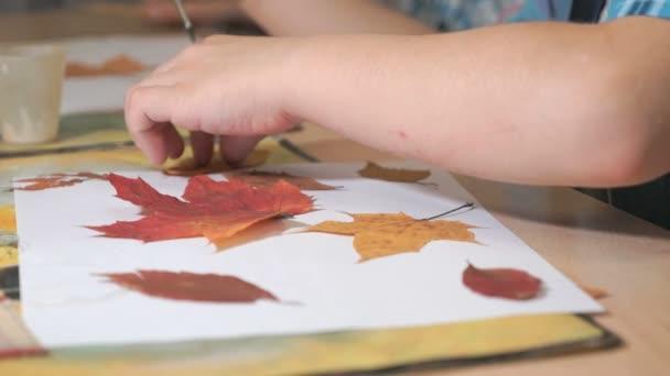 Bambino che fa erbario dalle foglie. Close-up