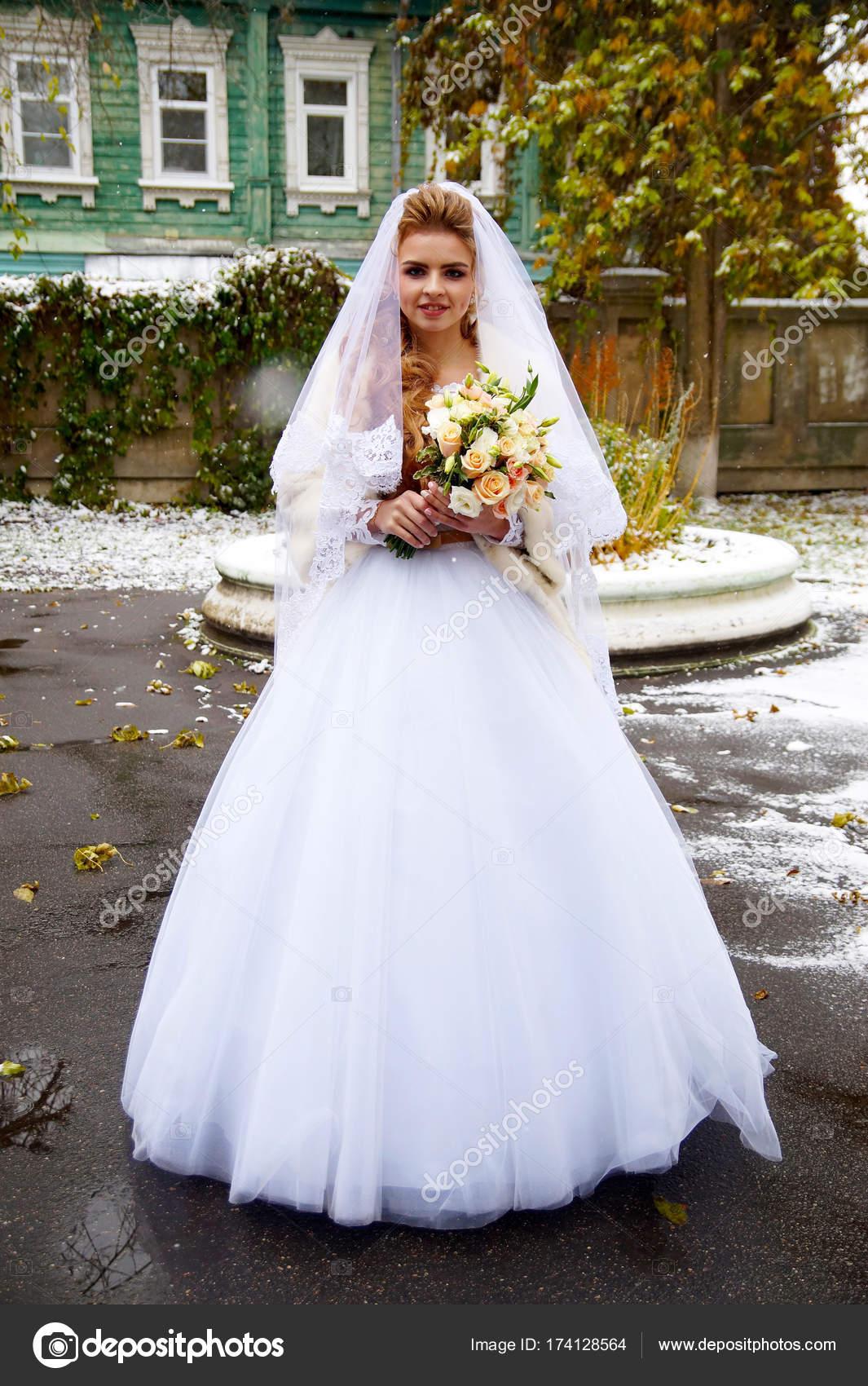 Beautiful young bride posing in a wedding dress — Stock Photo ...