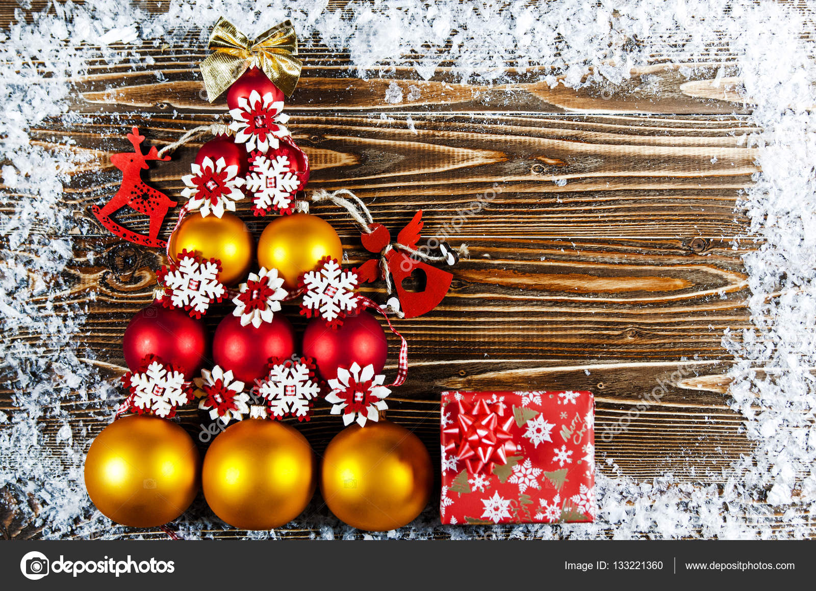 Christmas Tree Lined With Red And Gold Balls Toys Lie On A Wooden Surface Next To The Is Gift Toy In
