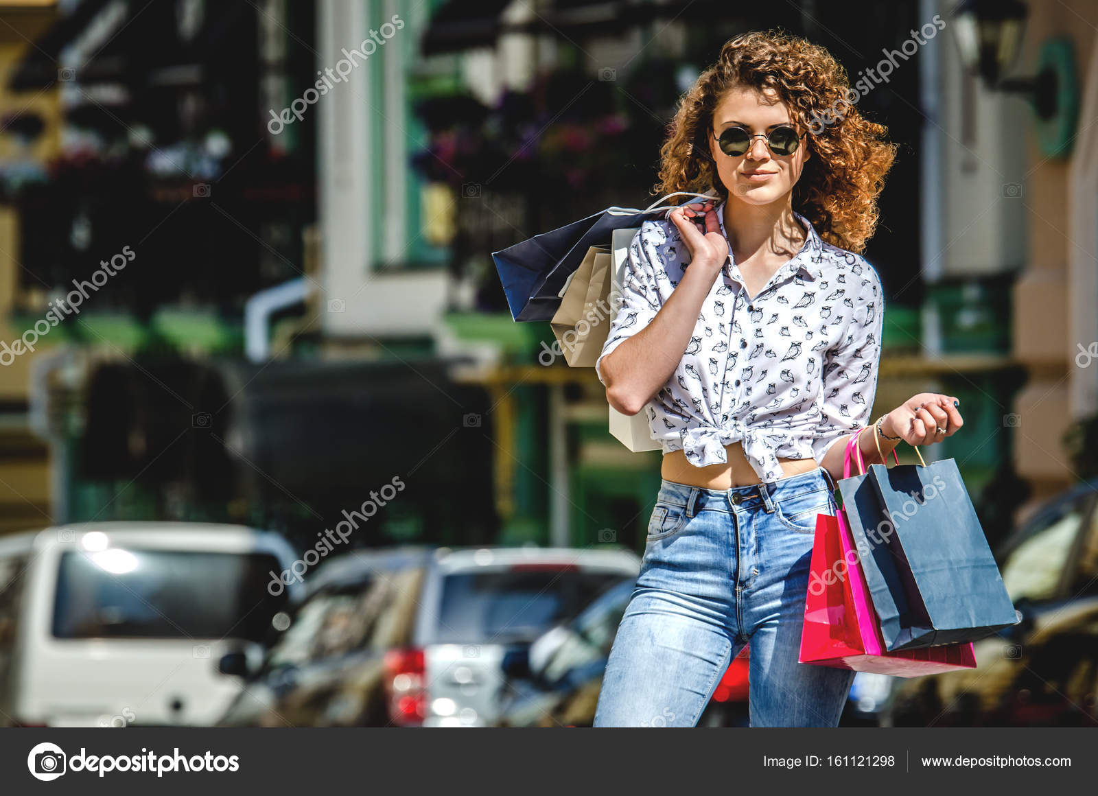 801d5a7b42 A young girl in round sunglasses with paper bags after shopping.– stock  image