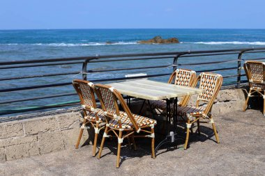 "Картина, постер, плакат, фотообои ""стул и стол стоят в кафе на берегу Средиземного моря в Израиле "", артикул 321876074"