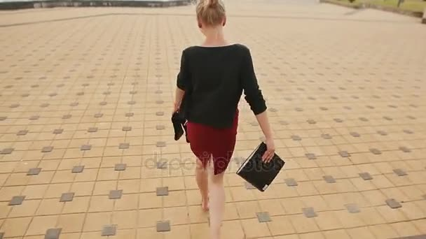 Beautiful girl businesswoman barefoot with shoes and a folder in his hands after a hard day of skipping.