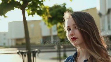 Szép fiatal lány megy keresztül a város, a naplemente. A kéz tetoválás