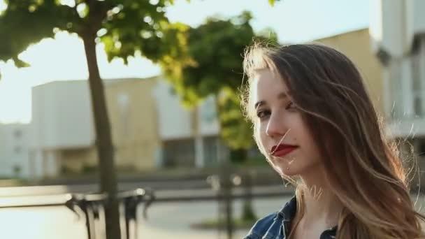 Krásná mladá dívka prochází městem při západu slunce. Na ruce tetování