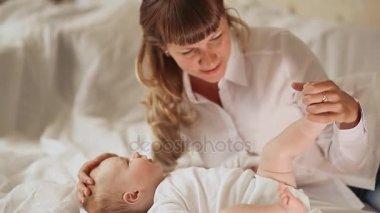 Matky ruce něžně líbat nožičky svého dítěte