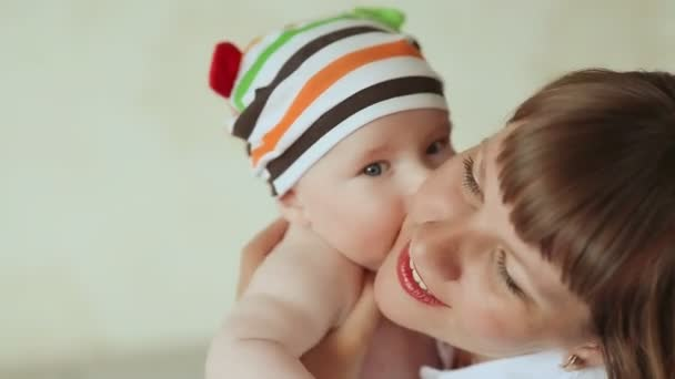 Baby tenderly kisses his mother. Dressed baby in striped shorts and cap