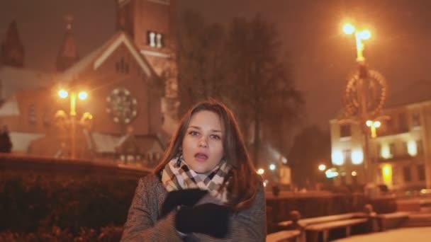 Mladá dívka na pozadí večer města zahřeje studené ruce. S ohledem na osvětlenou sněží