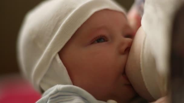 Kind in weiße Kappe saugt Brust Mütter
