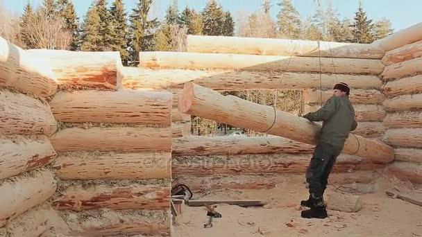 Carpenter nařizuje, že protokol je zvedáno jeřábem. Kanadský úhel zdiva. Kanadský styl. Dřevěný dům z břevna úpraveného cylindroidem