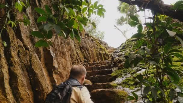 Muž turistické lezení po schodech do skály. Krásná příroda. Vietnamské džungle poblíž Elephant Falls