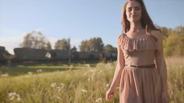 Krásná dívka s dlouhými vlasy jde na zelené louce a dotkněte květiny. Vír, vychutnat. V pozadí je předávání vlaku.