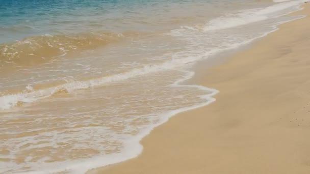 Mořská vlna na tropické pláži pískem zblízka.