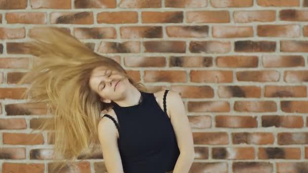 Hip hop blond dívka tančí v moderním stylu přes městské zdi. Zpomalený pohyb