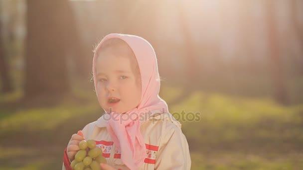 Ruská holčička v růžový šátek jíst hrozny při západu slunce