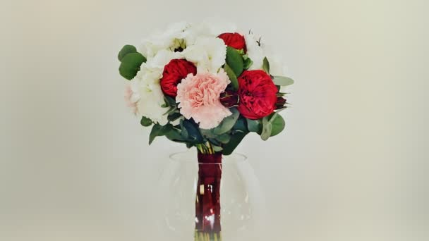 A wedding bouquet of hydrangea, pion-shaped rose, carnation and eucalyptus greens. Bouquet in rotation.