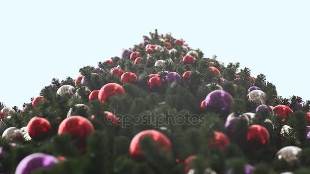 Vysoký vánoční strom v barevné koule. Sníh padá. Pohled na vánoční stromeček od zdola nahoru. Nový rok téma