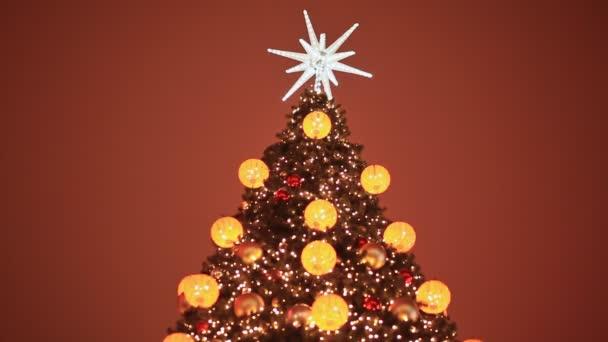 geschmückter Weihnachtsbaum in Spielzeug für Weihnachten in Moskau auf der Straße. leuchtende goldene Kugeln und Girlanden an den Zweigen. Jahresthema.