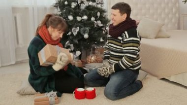 The guy gives the girl Christmas gifts. Cozy homely atmosphere.
