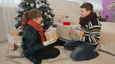 Young couple admire Christmas presents and give the viewer