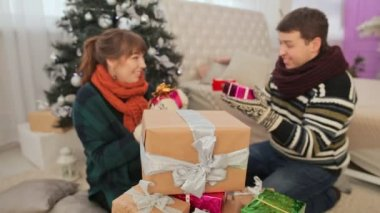 The guy and the girls take gifts from the pile of presents and show off to them the viewer. Christmas theme.