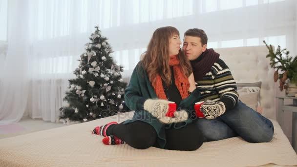 Milující pár sedí na posteli a pohodu zahřeje, užívali si jeden druhého. Pijí horkou kávu. Štědrý den. Příjemnou atmosféru New Years