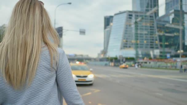 Dívka v centru města úlovky taxi nebo projíždějící auto