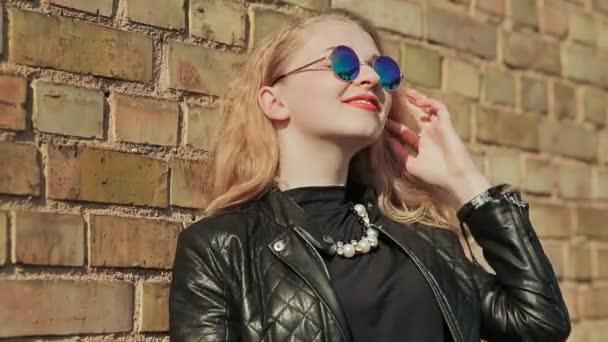 Elegantní Mladá blondýnka v sluneční brýle a černou koženou bundu poblíž cihlovou zeď na ulici