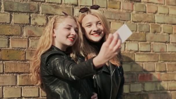 Két barátnő, napszemüveg és elegáns bőr kabát egy fotót egy mobil telefont, egy tégla fal mellett az utcán. Csinál selfie
