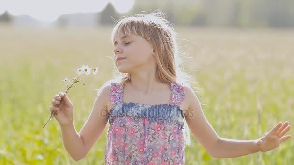 Krásné světlé a blond holčička s květy heřmánku v rukou pózuje a spinning v letním dni.