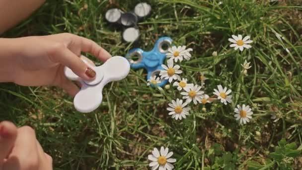 junges Mädchen spielt an einem sonnigen Sommertag mit einem weißen Spinner auf dem Rasen.