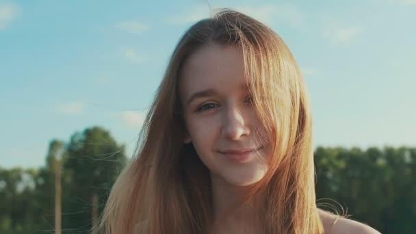 Fiatal lány mosolyogva tökéletes mosoly és a fehér fogak, egy parkban, és látszó-on fényképezőgép