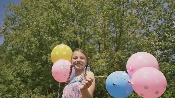 Mladá dívka s vzdušné barevné míčky s úsměvem a Pózování na kameře. Dobrou náladu a pozitivní.