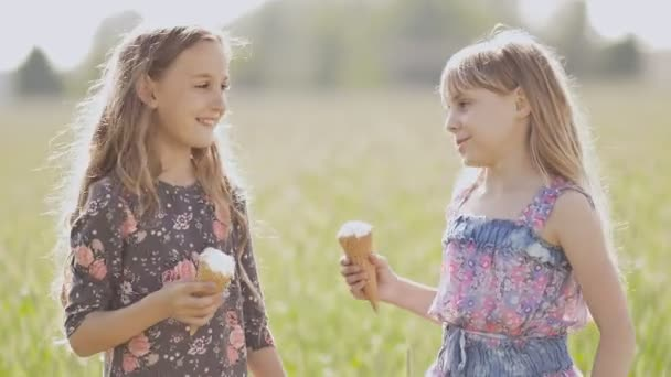 Two little girls sisters posing and hugging holding ice cream in the summer on a sunny day. Two best friends.