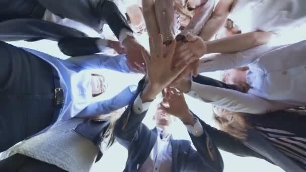 College Studenten Teamwork Stapeln Hand-Konzept. Freundlichen Absolventen der senior School legen Sie ihre Hände auf einander und öffnen Sie sie gegen den weißen Himmel. Sonnigen Tageslicht
