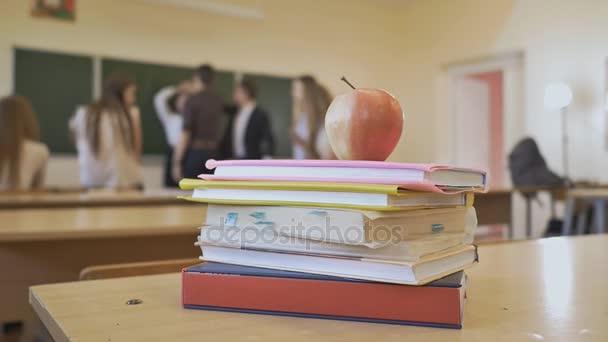 Školní přestávky v učebně. Knihy s apple jsou na stole. Téma škola.
