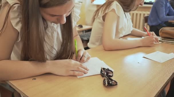 Russian school. Pupils write a control exam in their notebooks.
