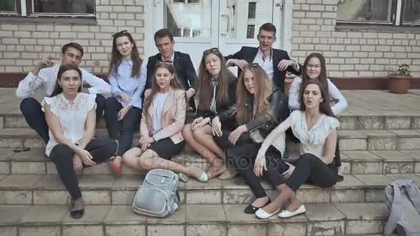 Studenti sedí na schodech školy a mávat rukama. Skupina budovy vysoké školy studenti sezení venku