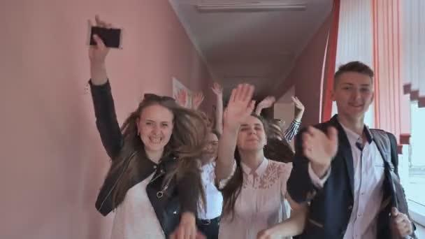 Glückliche Gruppe von Oberstufenschülern läuft über Flur