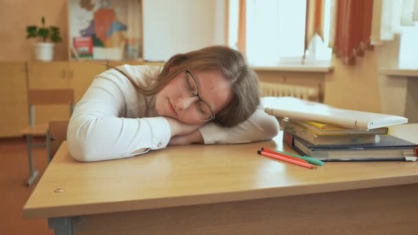 Tired student girl with glasses sleeping on the books in the class